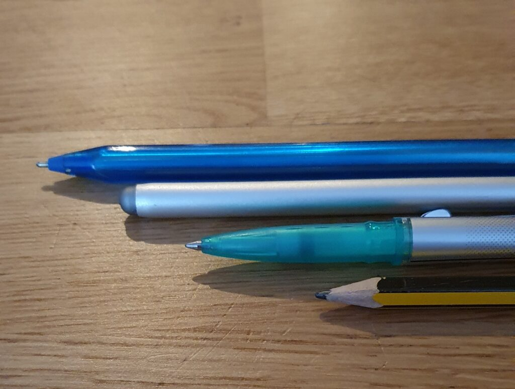 A selection of pens, pencils and a stylus, used for freelance editing & copywriting