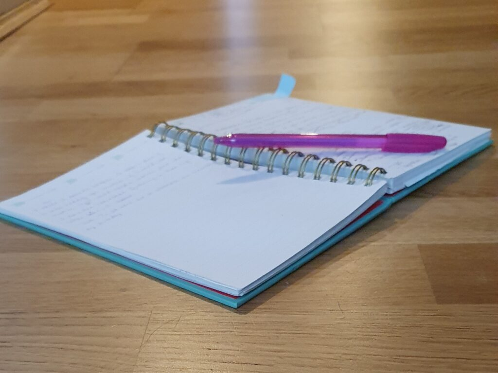 A pen rests on an open notebook, used for freelance editing & copywriting.