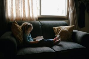 A girl reclines on a couch with a book