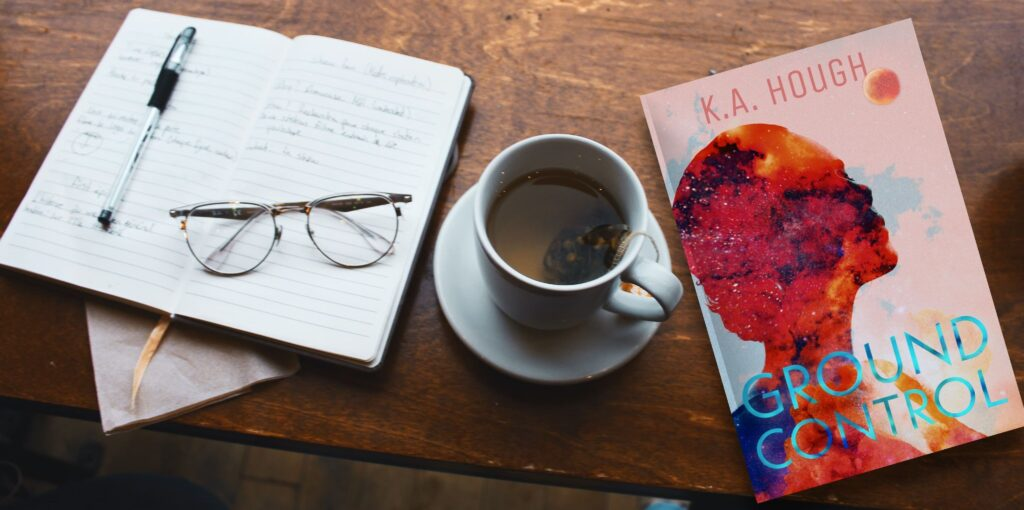 KA Hough's Ground Control sits on a table beside a cup of tea and an open notebook, on which a pen and glasses rest.