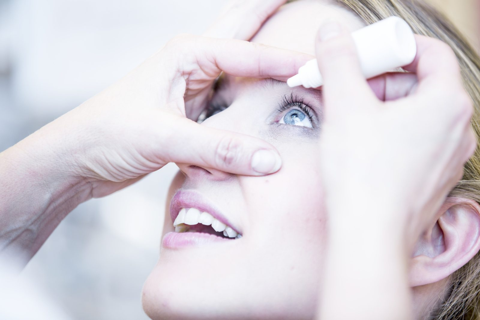 Close-up of person applying eye drops.