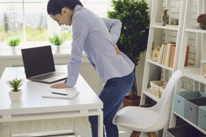 Woman experiencing low back pain while standing at her desk at work