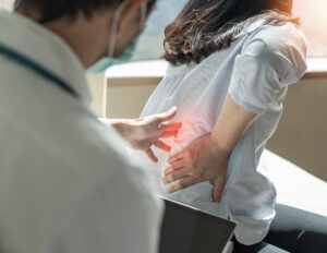 Doctor examining woman with painful spinal compression fracture