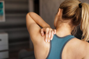 Athletic woman feeling pain in her neck after home workout