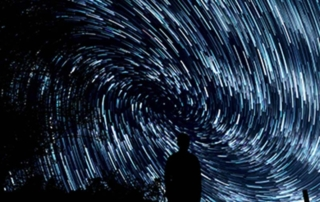 Photo Credit, Jeremy Thomas, a black silhouette of person looking at gyre of stars