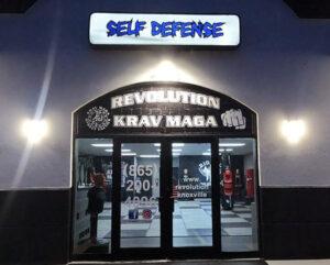 entrance door of Revolution Krav Maga lit up at night