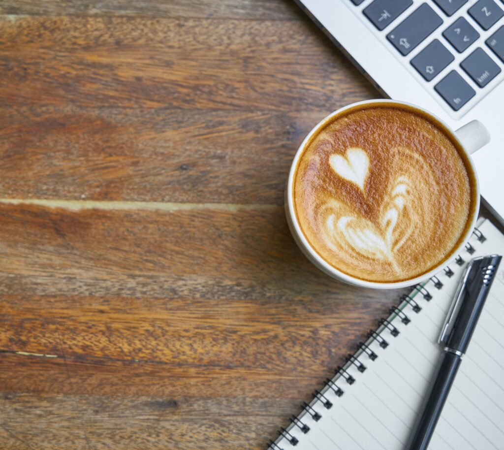 notebook, pen, computer and a cappuccino with a heart