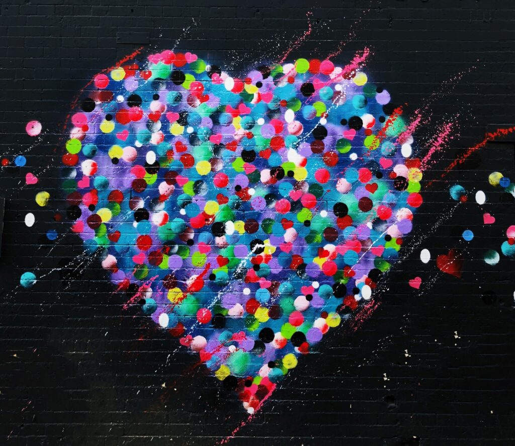 heart with a lot of colors, painted on a black wall