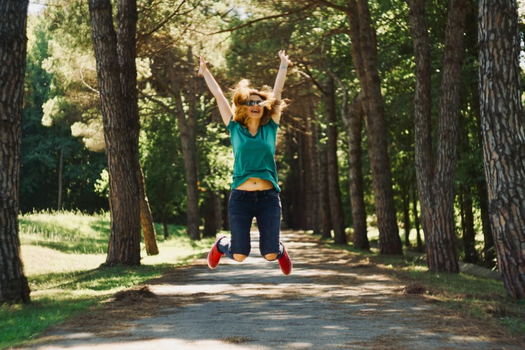 happy woman jumping with trees around her