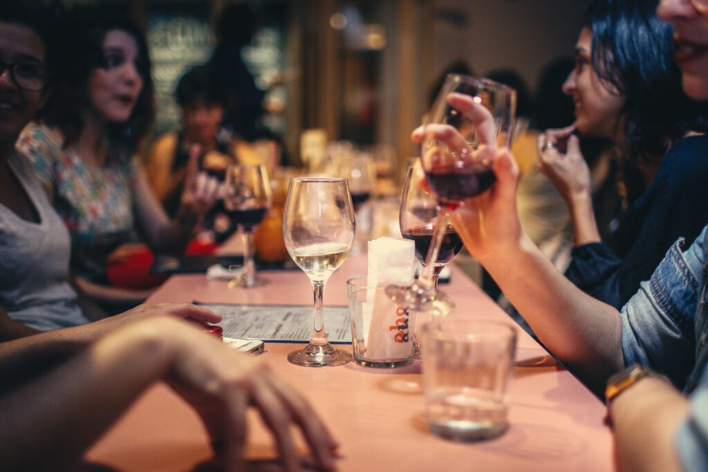 people with glasses of wine, chatting around a table in a restaurant