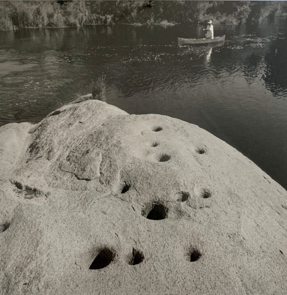 Dave Koehler canoes by a large bedrock mortar in the San Joaquin River