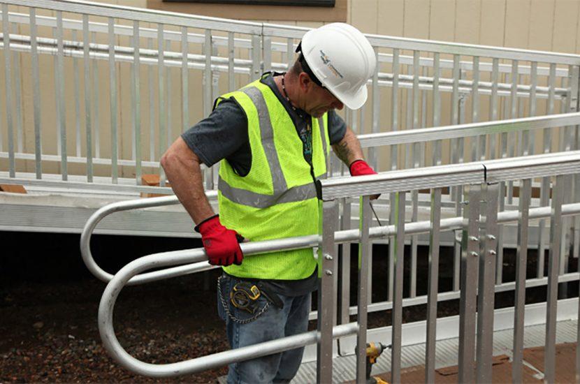 Man installing handrail on wheelchair ramp