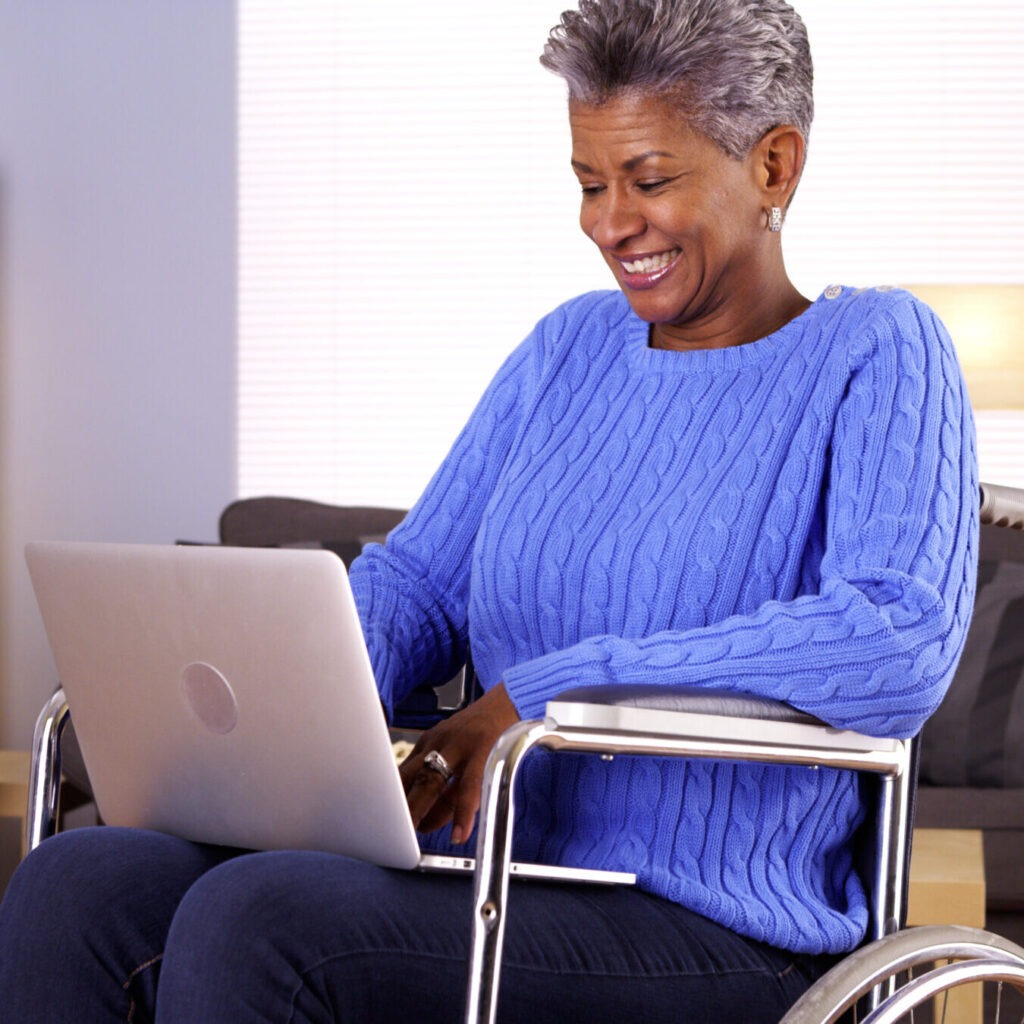 Photo of woman sitting in a wheelchair while using a laptop computer