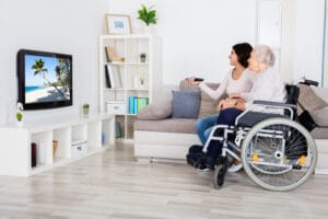 Elderly woman in wheelchair watching television with younger woman