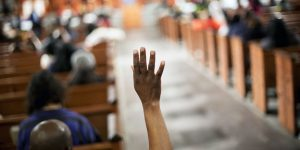 Morma Francis, of Atlanta, raises her hand to ask a question during a community town hall forum at Ebenezer Baptist Church, the church where The Rev. Martin Luther King Jr. preached, Monday, Dec. 8, 2014, in Atlanta. Dozens of people met at the church to discuss recent cases of unarmed black men being fatally shot by police and ways to improve the way officers interact with the public.(AP Photo/David Goldman)