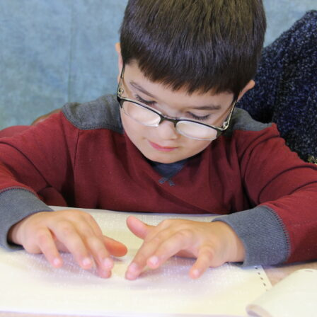 Boy reading braille