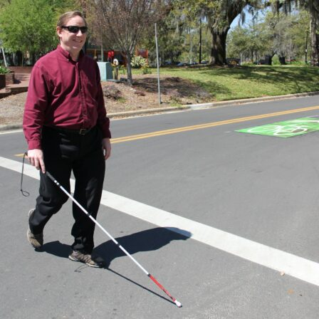 man crossing at cross walk with a cane