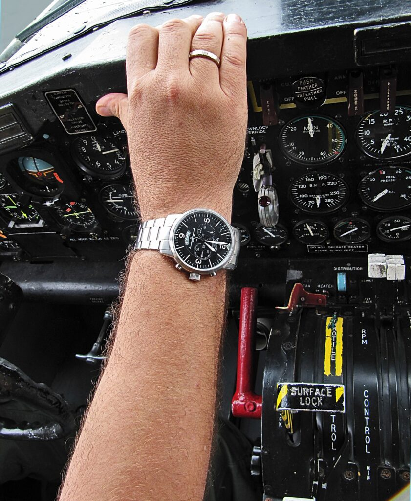 Pilot watch on the arm of a pilot, to illustrate the importance of the report time in the life of a pilot.