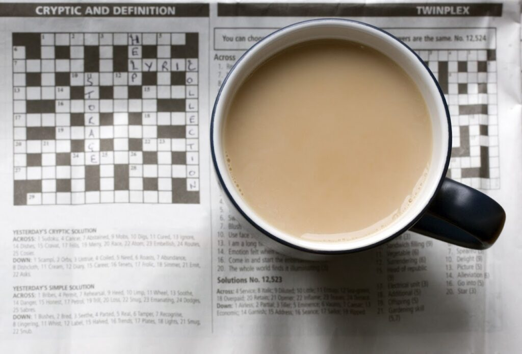 A cup of coffee on top of a crossword page of a newspaper