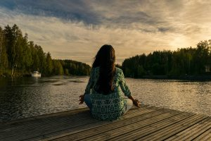 Woman sitting on a dock during sunrise