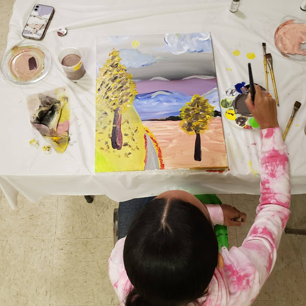 A girl in a tie-dye design jacket finishing her painting