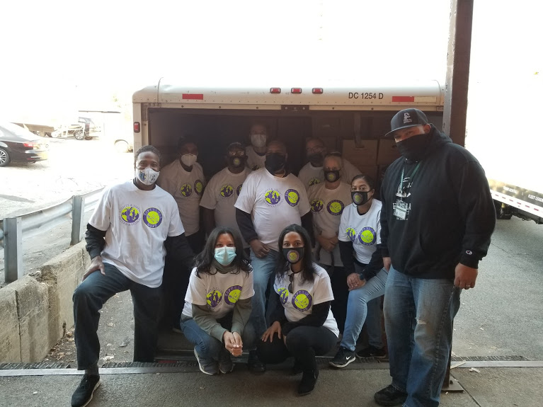 Esperanza-Hope staff wearing white shirts and masks, posing in front of a truck with boxes
