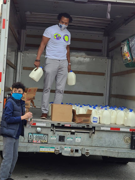 One of our male staff holding two gallons of milk inside a truck full of gallons of milk