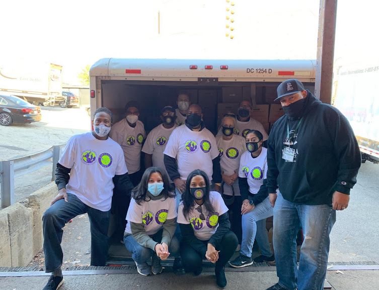 Esperanza-Hope staff wearing white shirts and masks, posing in front of a truck with boxes, 2
