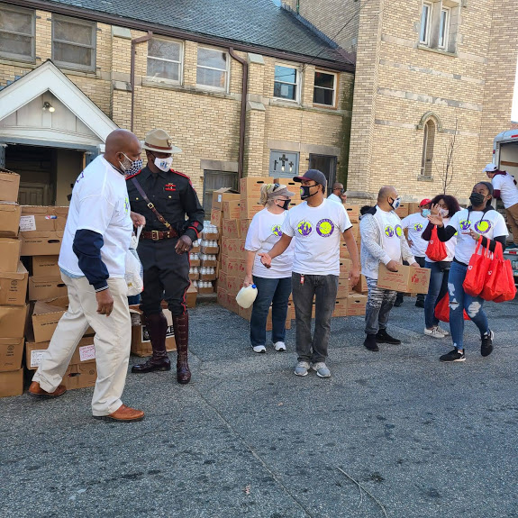 A group of people (staff) carrying boxes, bags, and a police officer standing