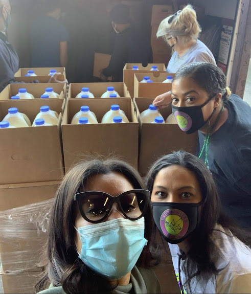 Four female staff with boxes of gallons of milk behind them