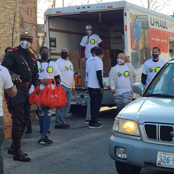 A group of our staff walking, one carrying bstrong bags, a police officer, and an open truck with boxes at the background