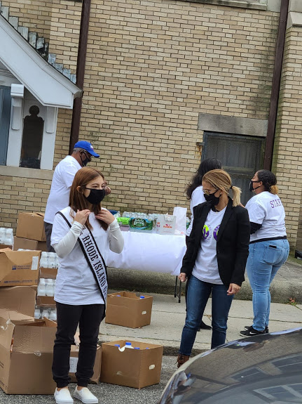 Ms. Rhode Island and some of our staff with boxes of gallons of milk on the road