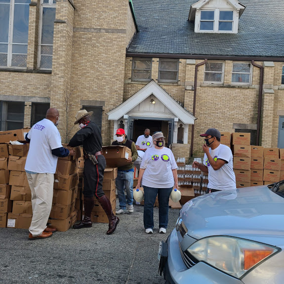 Our staff carrying gallons of milk, boxes, a police officer helping us, and a car passing by