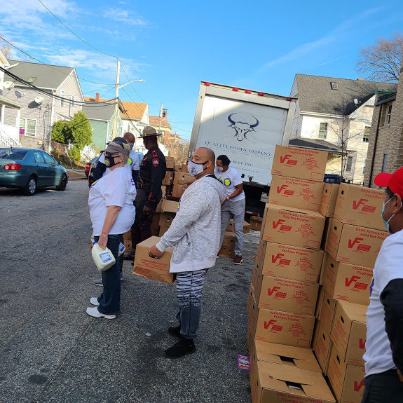 Our staff carrying boxes of food and gallons of milk waiting to cross the street