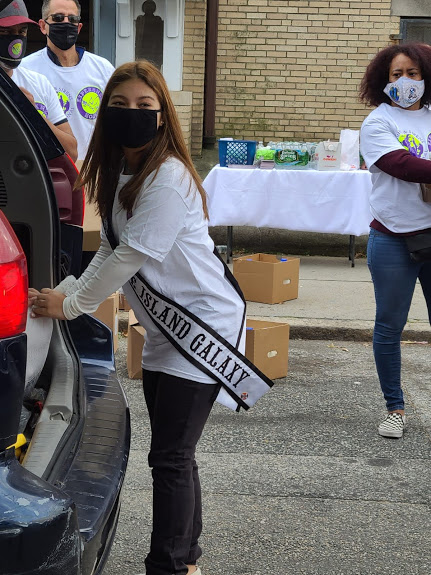 Ms. Rhode Island picking up a gallon of milk from a car trunk