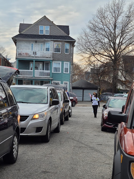 Cars lined up and a blue house at the background