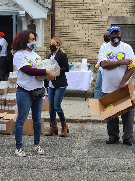 A female staff carrying a box of bottled milk and a male staff with a box