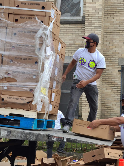 A male staff standing at a truck with stacks of boxes