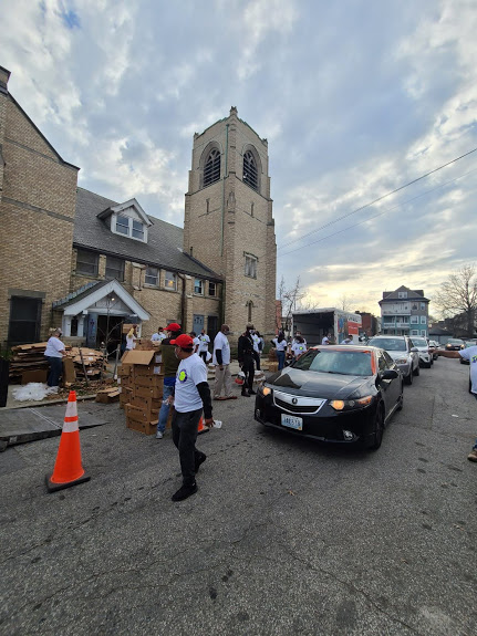 Cars pass by as our staff continue to carry boxes to the church