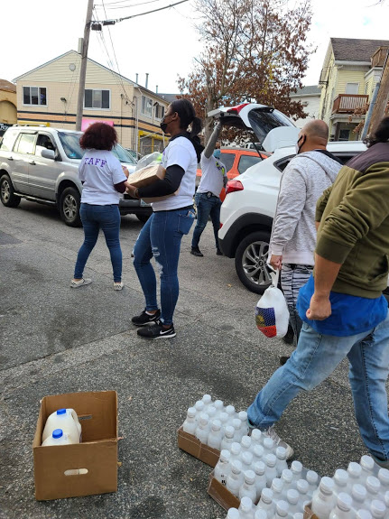 Our staff carrying boxes and bags of food and walking across the street