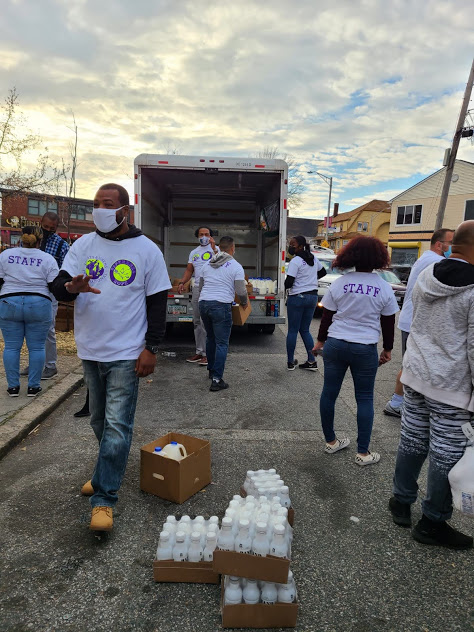 Our staff standing and carrying boxes from the truck while some milk boxes are on the road