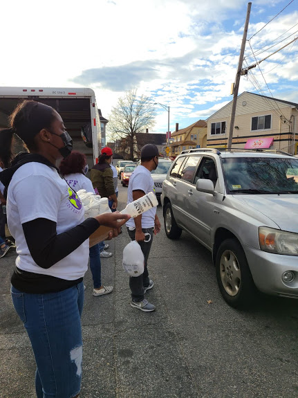 Our staff holds a box of bottled milk and another staff holds a bag of food as cars pass by