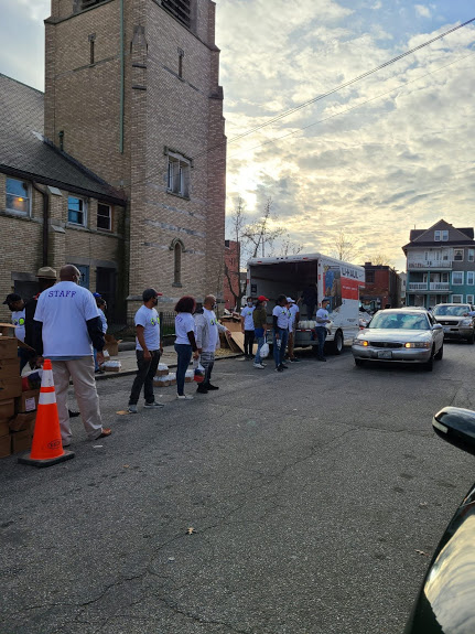 Our staff lined up and holding boxes of food and bottled milk for the cars passing by