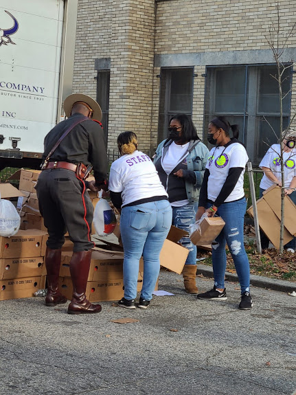 A group of female staff and the church guard getting bags of food from one of the boxes