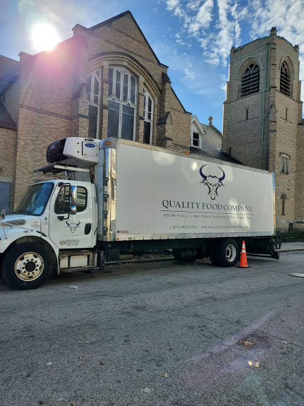 A Quality Food Company truck in front of the church