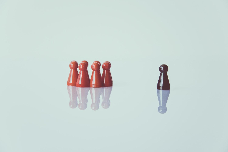 À esquerda, 4 peças de jogos de tabuleiro reunidas. À direita, uma peça preta.