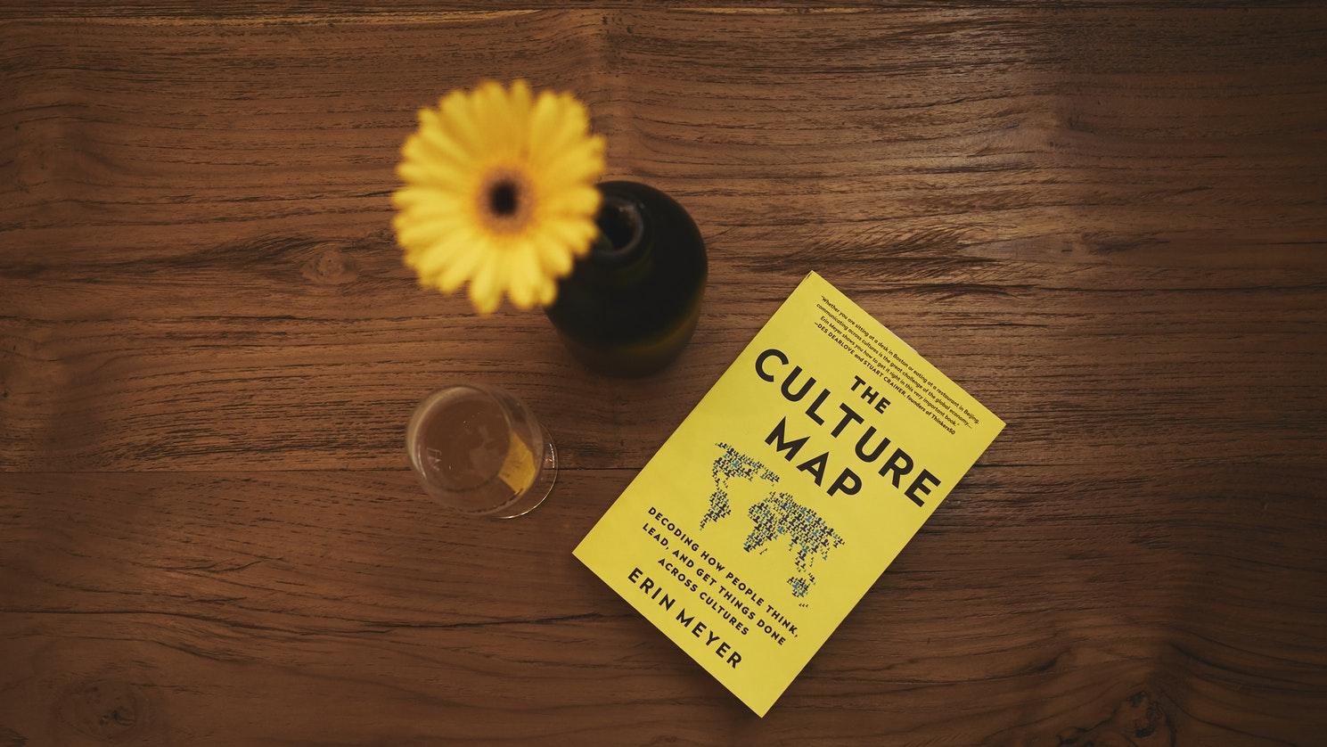 """Vaso de flor amarela e papel amarelo escrito """"the culture map"""" sobre mesa de madeira"""