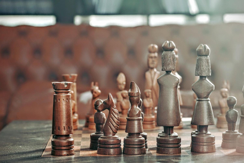 Peças de xadrez em tabuleiro com sofá ao fundo