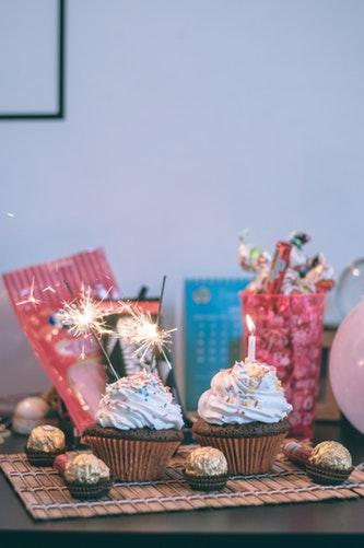 Mesa com cupcakes com velinhas de aniversário e vários doces