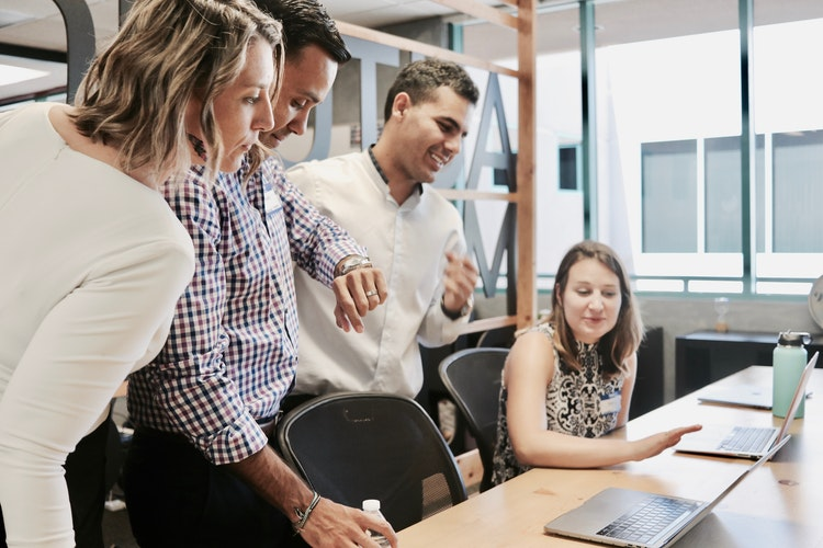 Quatro pessoas em uma sala, duas mulheres e dois homens. Uma mulher encontra-se sentada de frente a uma mesa apontando para um notebook, enquanto os outros 3 encontram-se de pé.